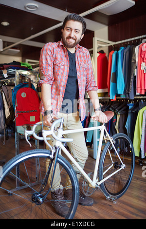 Portrait of a handsome man with bicycle looking at camera in sports shop - Stock Photo