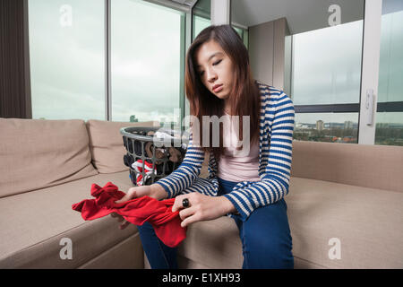 Young woman doing laundry work in living room at home - Stock Photo