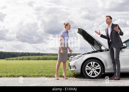 Full length of business couple having argument by broken car at countryside - Stock Photo