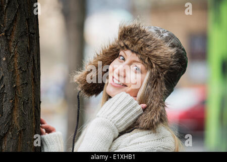 Portrait of beautiful young woman wearing fur hat outdoors - Stock Photo