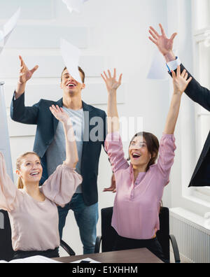 Businesspeople throwing papers in the air at office - Stock Photo