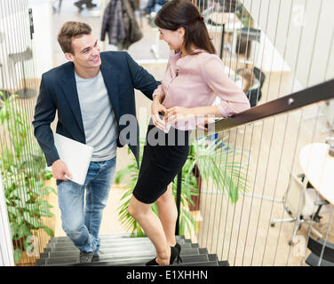 Full length of young business couple on staircase - Stock Photo