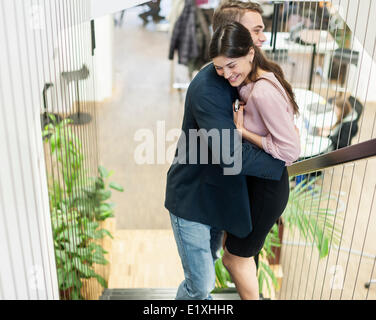Side view of young business couple hugging on staircase - Stock Photo