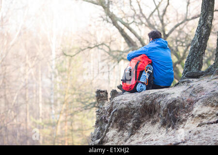 Rear view of hiker with backpack sitting on edge of cliff in forest - Stock Photo