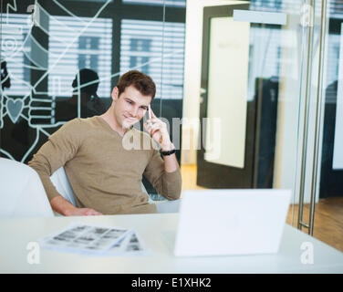 Handsome young businessman using smart phone in office - Stock Photo