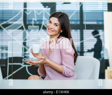 Portrait of confident businesswoman having coffee in office - Stock Photo