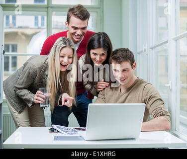 Happy business people using laptop in meeting - Stock Photo