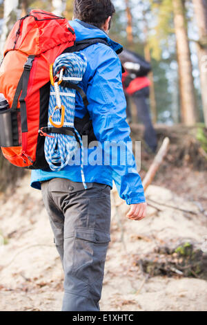 Rear view of male hiker with backpack standing in forest - Stock Photo