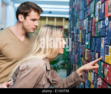 Business couple reading information about models on board in office - Stock Photo