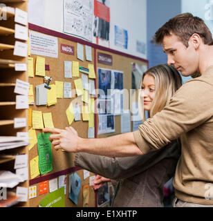 Business people reading reminders on bulletin board in office - Stock Photo