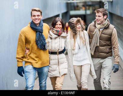 Happy friends walking together in lane - Stock Photo