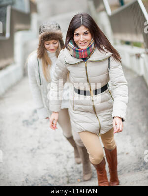 Full length of beautiful woman climbing stairs with friend outdoors - Stock Photo