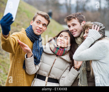 Smiling couples taking self portrait through cell phone in park - Stock Photo