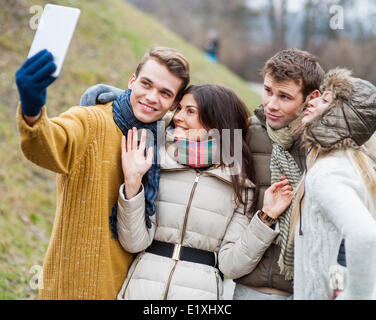 Happy couples taking self portrait through cell phone in park - Stock Photo