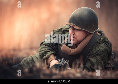 Young man in Red Army form posing with the PPSh-41 (Soviet submachine gun) - Stock Photo
