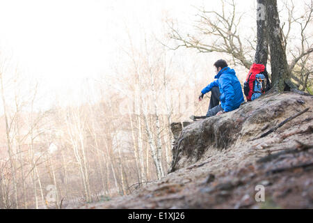 Side view of male hiker sitting on edge of cliff in forest - Stock Photo