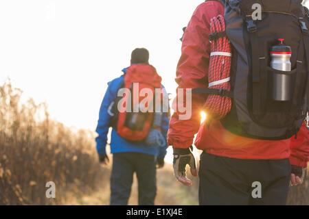 Rear view of male backpackers walking in field - Stock Photo