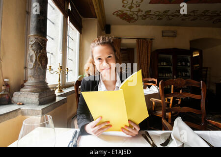 Smiling customer holding menu at restaurant table - Stock Photo