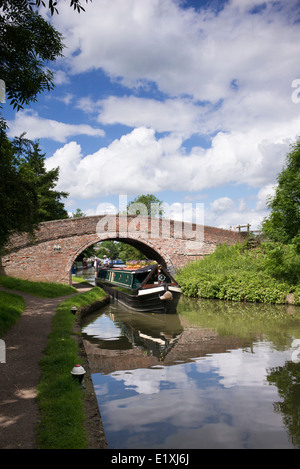 Narrowboat going under a bridge on the Grand Union Canal at Braunston, Northamptonshire, England - Stock Photo