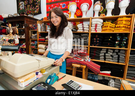 Portrait of smiling young female salesperson at checkout stand in gift store - Stock Photo