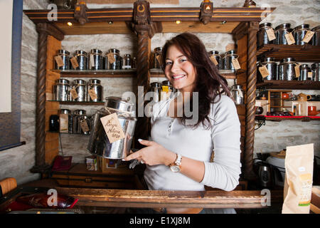 Portrait of smiling salesperson displaying tea container in store - Stock Photo