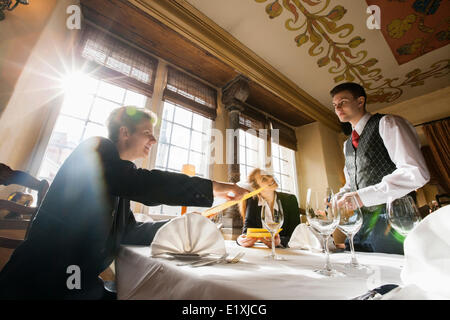Smiling business couple ordering food at restaurant table - Stock Photo