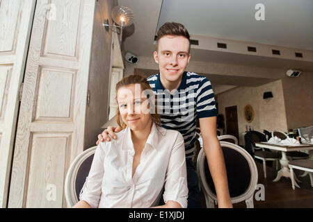 Portrait of young couple in restaurant - Stock Photo