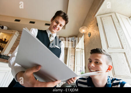 Low angle view of waiter showing menu to male customer in restaurant - Stock Photo