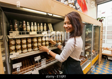 Portrait of smiling saleswoman arranding products in supermarket - Stock Photo