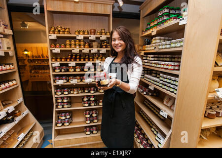 Portrait of happy saleswoman showing product in grocery store - Stock Photo