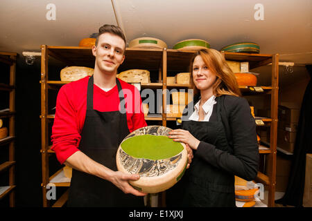Portrait of confident salespeople showing cheese in shop - Stock Photo