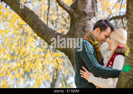 Side view of young couple hugging near autumn tree in park - Stock Photo