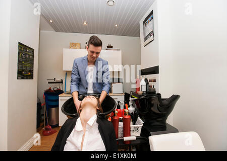 Male hairstylist washing female customer's hair in beauty salon - Stock Photo