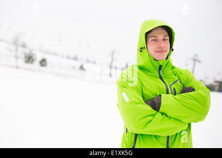 Portrait of young man in hooded jacket standing arms crossed in snow - Stock Photo