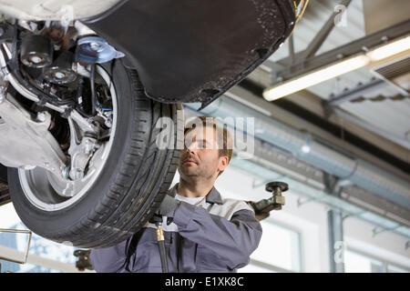 Mid adult technician repairing car's wheel in workshop - Stock Photo