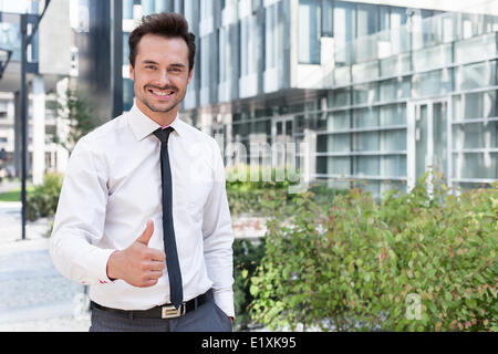 Portrait of happy businessman showing thumbs up outside office building - Stock Photo