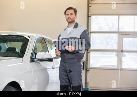 Portrait of confident male mechanic with clipboard standing by car in workshop - Stock Photo