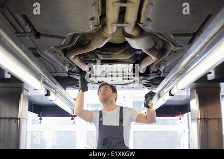 Mid adult male repair worker repairing car in workshop - Stock Photo