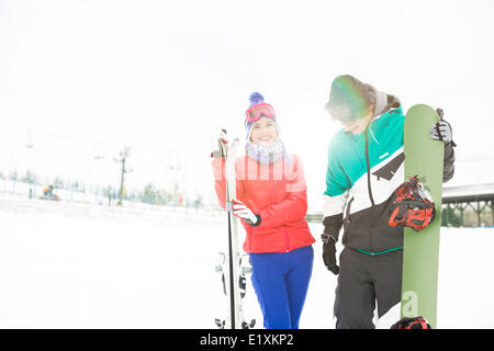 Happy young couple with snowboard and skis in snow - Stock Photo