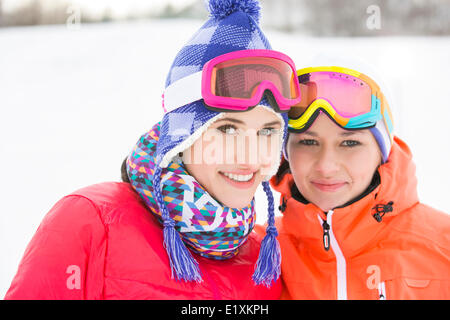 Portrait of happy young female friends in warm clothing outdoors - Stock Photo
