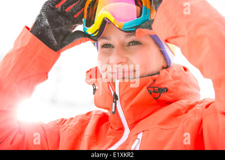 Young woman wearing ski goggles outdoors - Stock Photo
