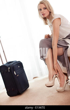 Full length portrait of young businesswoman taking off her shoes in hotel room - Stock Photo