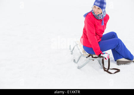 Beautiful young woman sitting on sled - Stock Photo