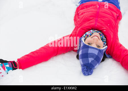 Portrait of smiling young woman lying on snow - Stock Photo