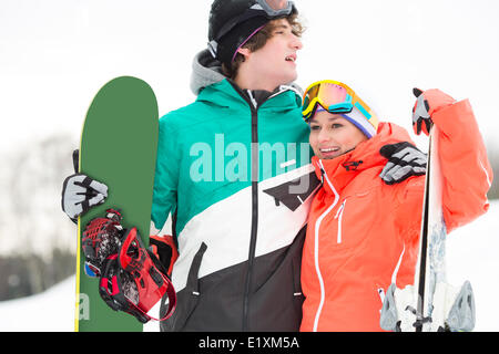 Young couple with snowboard and skis in snow - Stock Photo