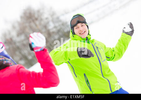 Happy young man throwing snowball towards woman