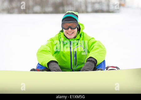 Portrait of smiling young man with snowboard sitting on snowy land - Stock Photo