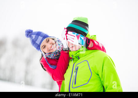 Smiling young woman covering man's eyes in winter - Stock Photo