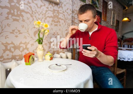 Man having coffee while reading text message on cell phone at cafe - Stock Photo