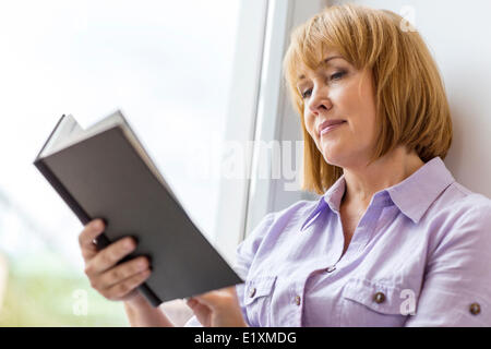 Mature woman reading book by window at home - Stock Photo